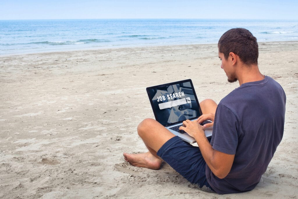 digital nomad working on the beach