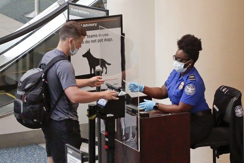 TSA worker checks passenger at Orlando International Airport